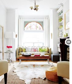 Living room in a victorian house with stain glass window, modern furniture, hide rug. http://cococozy.com