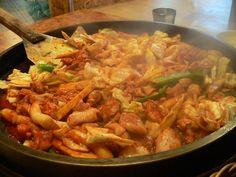 El dak galbi es un plato popular en Corea del Sur que suele hacerse salteando dados de pollo marinado y rodajas de repollo, papa, cebolla y tteok (pastel de arroz) sobre un plato caliente.