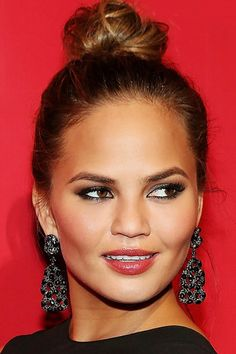 Chrissy Teigen is a bombshell with a tight bun, coral lips and a smoky eye
