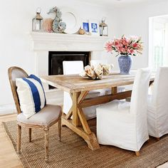 From the whitewashed wood dining table to the beachy mantel display, this dining room is filled with cottage-style appeal. White slipcovers on the dining chairs can be easily removed for washing. Casual Dining Rooms, Dining Room Blue, Dining Room Design, Dining Chairs, Dining Table, Wood Table, Dining Area, Trestle Tables, Rustic Table