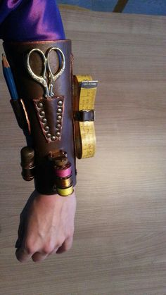 The bracer I wear on the left side with a lovely pair of embroidery scissors, metal bobbins, a vintage measuring tape, pencils and a tube containing needles. It's made from 3 mm thick vegetable tan...