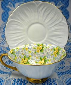 This is a Shelley China, England cup and saucer in the Low Oleander shape with the Primrose Chintz pattern with heavy burnished gold trim pattern with pale blue exteriors, number 13588. The gorgeous c