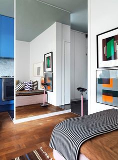 Small Colorful Apartment with Mirrored Wall Divider between Bedroom and Kitchen