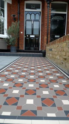 victorian mosaic garden tile path with yellow brick london wall