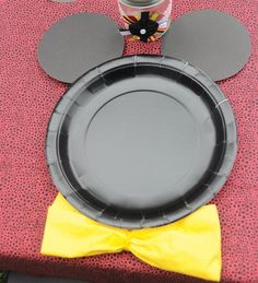 Mickey Mouse Party--black paper plates with circle cut-outs for ears. Add a napkin bow below the plate.