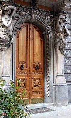 Linda porta de madeira, do tipo francesa, com detalhes decorativos esculpidos e parte superior em arco.