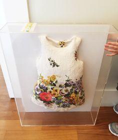 Vestido na moldura para recordação do primeiro ano da Maria Antonia. Vestido floral de menina Dolce & Gabbana no quadro de acrílico.