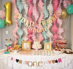 décoration anniversaire enfant - guirlandes en papier de couleurs pastel, gâteau blanc décoré d'étoiles et ballons multicolores