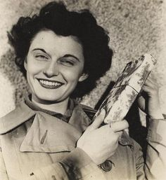 Emma Dale Love holding Christmas present, 1944. WAC Emma Dale (Newell) Love shakes one of her Christmas packages as they begin to arrive at the 12th Army Group Headquarters in France, November 11, 1944 ~