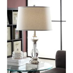 Improve a shadowy corner of your living room with this stylish table lamp. The crystal clear body of the lamp provides shine and style, while the big drum shade in cream linen and brushed nickel hardware keeps the piece very contemporary.
