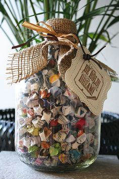 Recycled glass bottle filled with lucky origami stars from colorful magazine pages