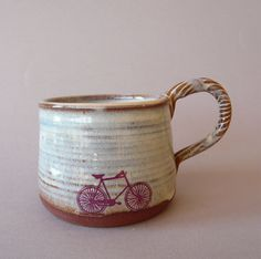 This mug measures 3.5 across by 3 tall. It was thrown and hand modelled then decorated with foodsafe glaze. The pink bike decal was fired into