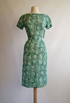 This is an adorable and sweet 1950s cotton eyelet dress with aqua flowers. It is fully lined but with a very sheer silk so you may want to wear