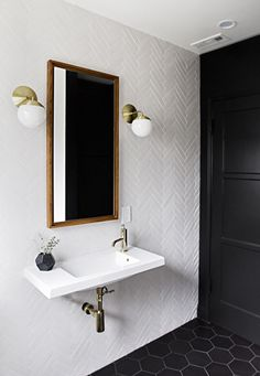 Herringbone tile wall with hexagon floor - so beautiful! Love the dark wall and brass accents too.