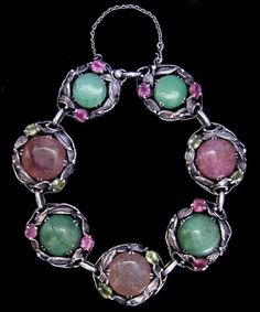 This is not contemporary - image from a gallery of vintage and/or antique objects. BERNARD INSTONE (1891-1987) A silver Arts & Crafts bracelet with jadeite and dyed crackle quartz antique Chinese buttons set in foliate settings decorated with peridots and tourmalines.