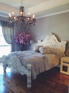 Beautiful white baroque tufted bed, chandelier, grey walls.
