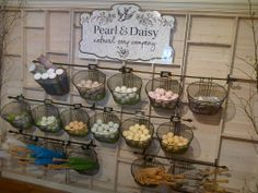 Bath bomb display. Classic metal wire bicycle baskets hung from black iron curtain rods. www.pearlanddaisy.com