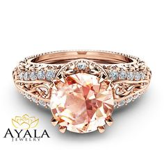 A stunning memento for your beloved! This morganite vintage engagement ring is a priceless statement of your love. Handmade in expert detail, this vintage rose gold ring is handcrafted with the utmost care and precision. It features a smooth band with a filigree and milgrain diamond encrusted accents along the top that holds the sparkling 2 carat morganite focal. Slip this on her finger for a guaranteed Yes!. Start your happily ever after the right way with Ayala Jewelry. Order now to…