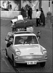 To kvinner og tre barn stikker hodet ut av bilvinduene på vei til ferie i juli 1960. Bagasjen er lastet på taket.  Aage Storløkken