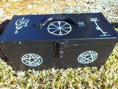 A simple metal toolbox with handle on top, re-purposed. Hand painted with devils traps and other sigils. The box itself measures approx. 16 x 7 x 7