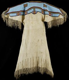 "30003 Sioux Woman's Dress, circa 1870  Full size dress with fringed sleeves and hem, two rows of thongs from skirt, beaded yoke with light blue ground, red, yellow and navy blue linear, rectangular and geometric forms. 58"" H x 48"" W including fringe as it hangs naturally"