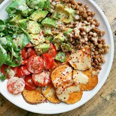 A vegan friendly salad bowl with lentils, roasted sweet potatoes, cherry tomatoes, lambs lettuce, avocado and a tahini dressing
