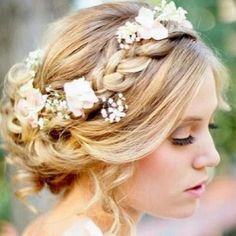 tossled curls twisted back into a messy loose bun, with a thick braid coming across one side. Perfect for a garden, vineyard or beach wedding. Minus the flowers