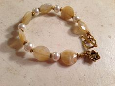 This cream bracelet created by Jewelry By Luet and Co is made of: cream acrylic beads, white glass pearls, gold plated: spacers, flower charm, toggle