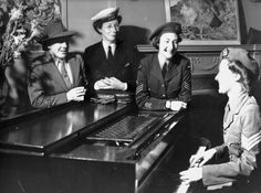 Unidentified group of women wearing World War II military uniforms, around a piano. Image taken between 1939-1945. Photographer and location unknown.