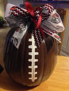 "Pumpkin football! Go Dawgs! ""Leather Brown"" spray paint on craft pumpkin, white acrylic paint for laces and cute bows."