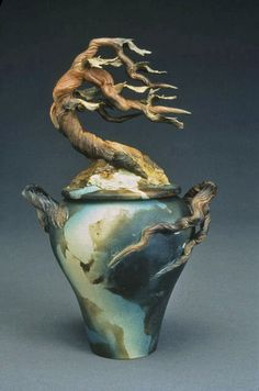 This amazing ceramic urn jar for the ashes of loved ones is adored with a a bent Cyprus Ginger Tree.   This is handmade by Bonnie in California via the wheel-throwing technique for the jar with the tree hand sculpted. Underglazed then smoke-fired finish. At www.spiritpieces.com