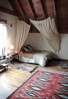 These curtains around the bed make a bed in a large room feel much more cozy.