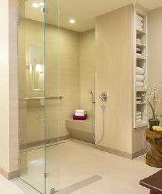 Many UD features are obvious throughout this bathroom space, including its attractive design. Features include a trench drain, a curb-less shower entrance, non- slip tile, a hand-held showerhead, and a shower bench.