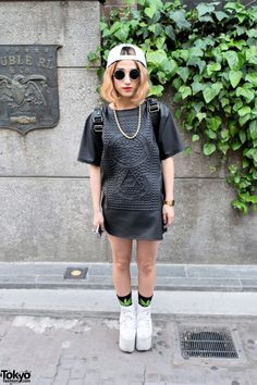 Tianba is a student who was met on Cat Street in Harajuku. She's wearing a UNIF faux leather embossed dress with graphic socks from the Japanese streetwear brand HUGE and YRU platform sneakers. Her hat is Supreme and her leather backpack is MCM. Other accessories include a gold chain, a wrist watch, and round sunglasses. (Tokyo Fashion, 2014)