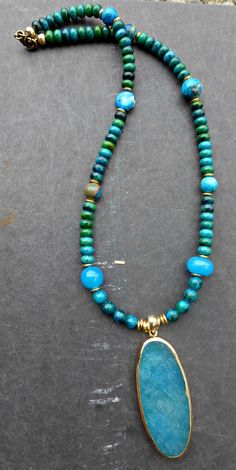 Pendant is blue agate stone with gold electroplating on the edges. Pendant is 2 inches long and 1 inch wide. With clay beads from India and bronze metal beads. Long necklace is like 25 inches As with