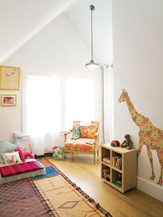 Whimsical furnishings in bright patterns, like floral giraffe wall decal and plush floor palette, make this Oakland playroom a perfect space for children. (Photo: Erika McConnell)