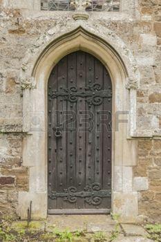 Alte dunkle Kirche Tür mit einem spitzen steinernen Torbogen in Stein gemeißelt