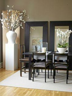 Mørke møbler og rene linjer dominerer spisestuen. Her er det små hint av Asia i form av kinesiske stoler fra Konzept HP ved bordendene, orkideer og kirsebærblomster. De andre spisestuestolene er arvet, men er trukket om og malt i svart bengalakk. Inntil veggen står to store speil og reflekterer veggkunsten på motsatt side.