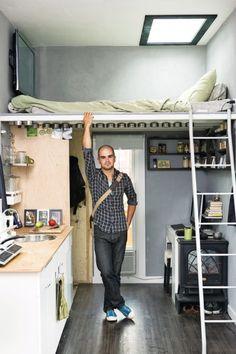 hombre que está en una habitación  con cocina sala y dormitorio en la parte superior