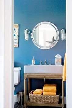 In a waterfront home, a nautical theme and beachy details like colorful towels feel breezy without going overboard. Upkeep is also a cinch thanks to to fingerprint-proof hammered-metal accessories. And doesn't that metal-framed mirror look just like a porthole? Click through for more bathroom decor ideas.