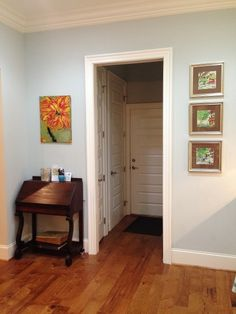 A little desk for charging phones finds a home in the kitchen with orange and green artwork adorning the walls.