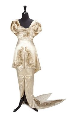 A cream satin embellished gown worn by Greer Garson, in Blossoms in the Dust (1941). The gown has a lampshade tunic with boning to bodice over a trained hobble skirt and is embellished with emerald colored and white rhinestones, gold sequins, and gold bullion in a feather motif. Costume design by Adrian.