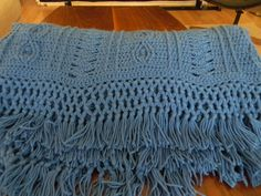From the description: Post stitches and puff stitches make a great cabled rope pattern on this sturdy throw. When you're through, try your hand at knotted fringe.