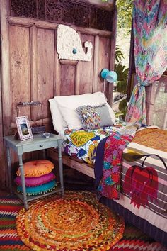 Pretty bohemian bedroom - perfect for a young teenage girl. Rustic timeber wall with carving detail, cute whale art work, bright stacked beaded cushions and electic linen.