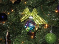 Holiday ribbon tied in a bow, curling ribbon curled and placed inside a clear glass ornament to match your theme.  Viola!