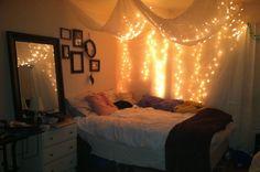 String lights under sheer drape over bed
