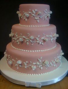 pink fondant with gumpaste rosebuds and royal icing piping. Ohhhhh.....I love this! So elegant.