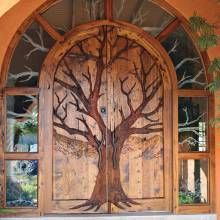 MAJORLY BEAUTIFUL!!!!  Grand Entry Doors - Phoenix Home & Garden  A tree motif is the focal point of this hand-carved door, which is crafted of hand-hewn exotic wood. The design extends onto the curving glass surround. Matching door pulls are made of hand-forged wrought iron.