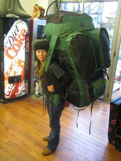 Looks are deceiving.  The model, Runtina Minimus, measures in at a mere 2 feet, 7 inches - despite her otherwise normal appearance. The vending machines behind her are props to provide the illusion of scale.  The pack that she is sporting is, in actuality, a small camera bag.