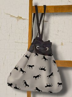 Equestrian themed shoulder bag or purse tote featuring galloping horses pattern in neutral black and beige colors to go with any fashion accessory.